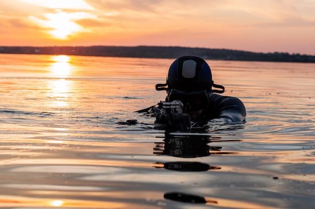Il combattente di un'unità speciale lascia l'acqua e si prepara per l'inizio dell'operazione. tecnica mista. il concetto di instabilità nel mondo, ostilità, crisi. russia vs usa Foto Premium