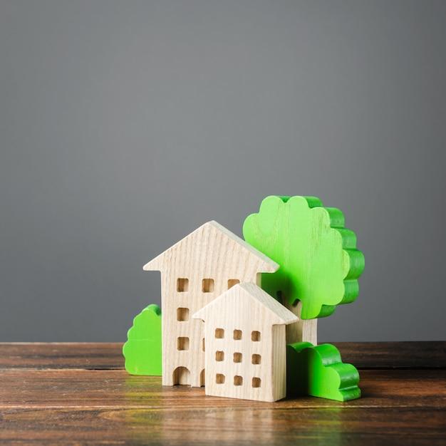 Figure di case e alberi. alloggio comodo ed economico. acquisto di appartamenti e immobili Foto Premium