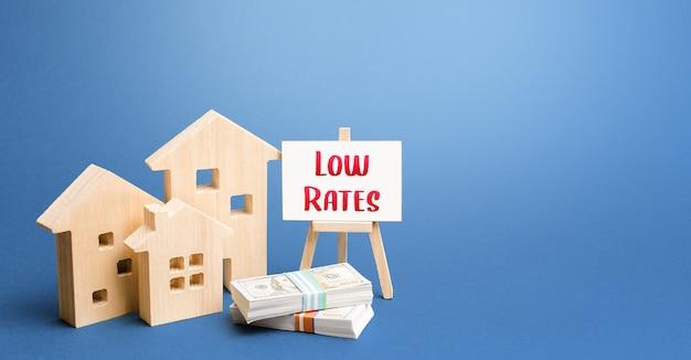 Figurine di case e un cavalletto con tariffe basse. bassa domanda di immobili e abitazioni Foto Premium