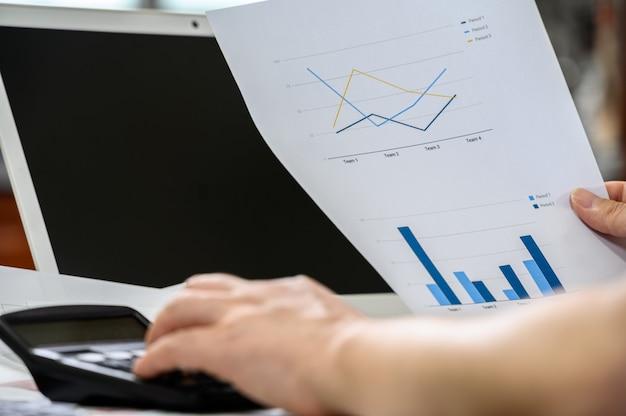 Finanza e concetto di affari. la mano dell'uomo d'affari che tiene il grafico finanziario. Foto Premium