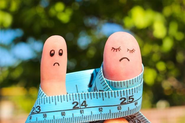 Arte del dito di coppia con metro. il concetto di uomo è magro, la donna è grassa. Foto Premium