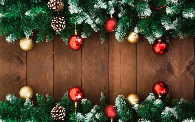 Rami di abete con decorazioni sulla vecchia superficie in legno scuro Foto Premium