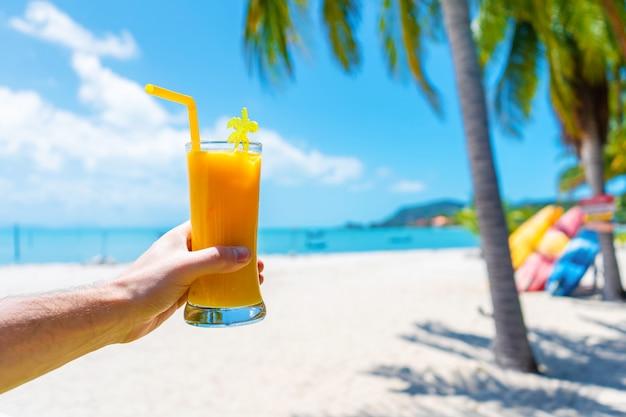 Visuale in prima persona. la ragazza tiene una tazza di vetro di mango freddo fresca sullo sfondo di una spiaggia tropicale di sabbia. sabbia bianca e palme. vacanza da favola Foto Premium