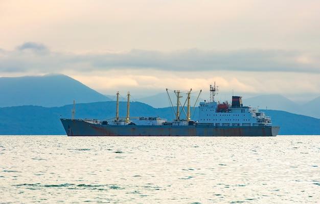 Barca da pesca in mattinata grigia sull'oceano pacifico al largo della penisola di kamchatka Foto Premium