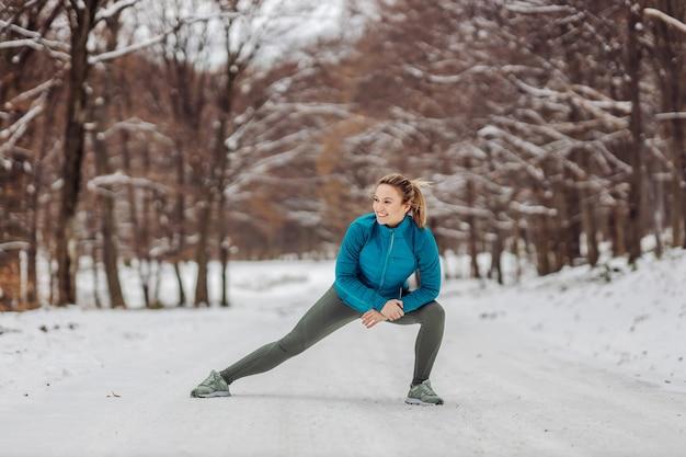 Sportiva in forma facendo esercizi di riscaldamento in natura su una neve. giornata di neve, fitness invernale, sport, esercizi sulla neve Foto Premium