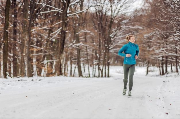 Fit sportiva in esecuzione in natura su un sentiero innevato. tempo freddo, neve, vita sana, fitness Foto Premium