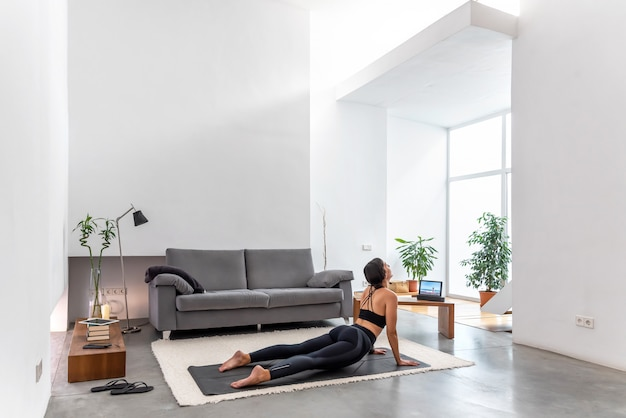 Posa adatta della pratica della cobra della donna facendo uso del programma online di addestramento di yoga nella compressa a casa Foto Premium