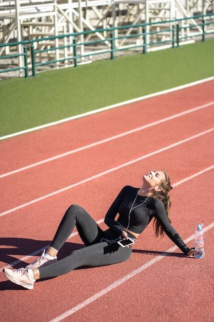 Montare la donna in abiti sportivi che riposa dopo l'allenamento o la corsa Foto Premium