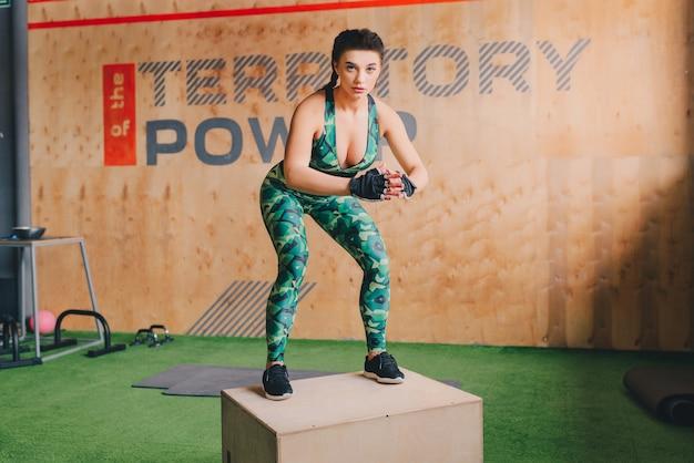 Scatola adatta della giovane donna che salta ad una palestra di stile del crossfit. l'atleta femminile sta eseguendo i salti della scatola alla palestra. Foto Premium