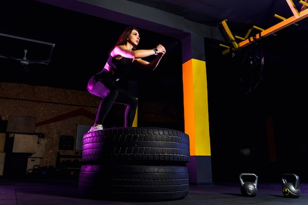 Scatola adatta della giovane donna che salta sulle gomme Foto Premium