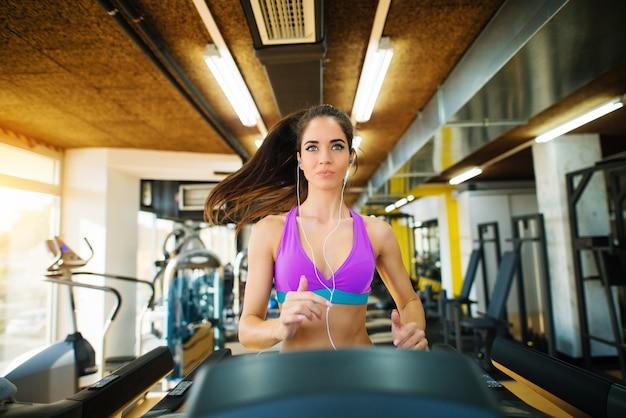 Bella ragazza attiva fitness in esecuzione sul tapis roulant e guardando dritto in palestra. Foto Premium
