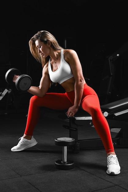 Ragazza di forma fisica con scavatori in posa su una panchina in palestra in abiti luminosi con una motivazione fitness top bianco e pantaloni rossi. Foto Premium