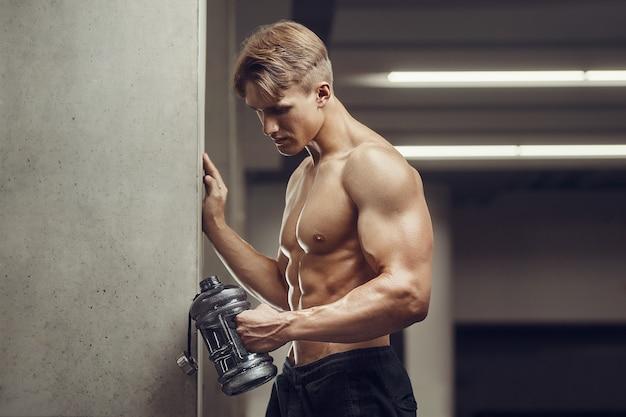 Uomo di forma fisica in acqua potabile palestra dopo l'allenamento guardando il telefono cellulare Foto Premium