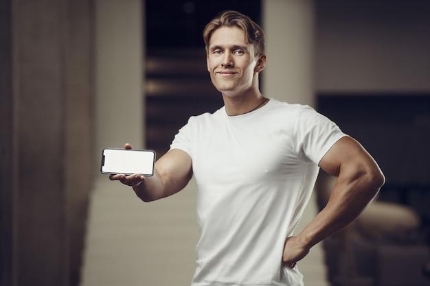 Uomo di forma fisica in palestra con il cellulare Foto Premium