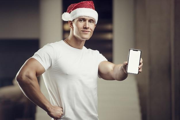 Uomo di forma fisica in costume del cappello di babbo natale in palestra con il telefono cellulare. buon natale e anno nuovo concetto Foto Premium