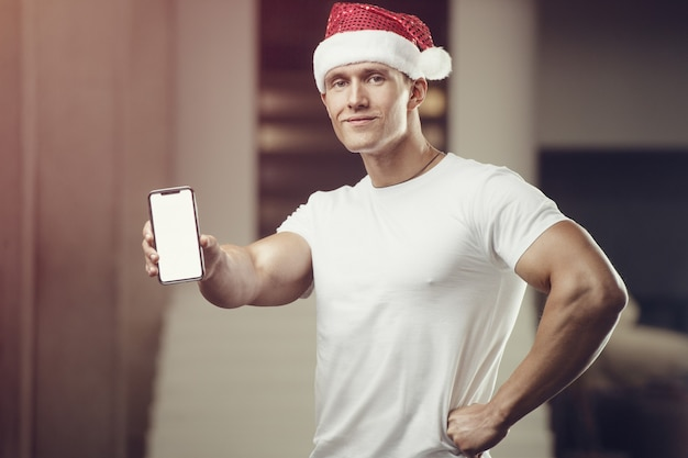 Uomo di forma fisica in costume del cappello di babbo natale in palestra con il telefono cellulare Foto Premium