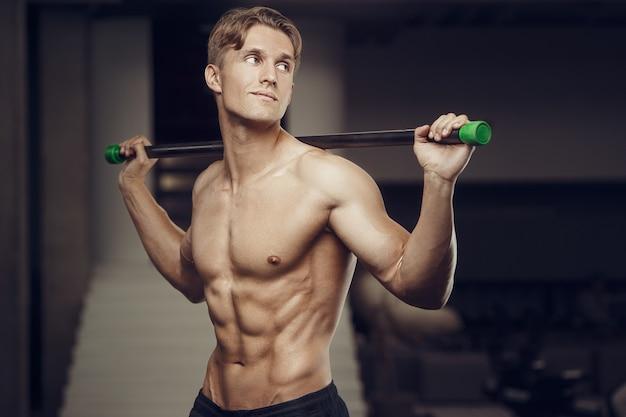 Uomo di forma fisica in allenamento in palestra con bodybar che allunga i muscoli Foto Premium