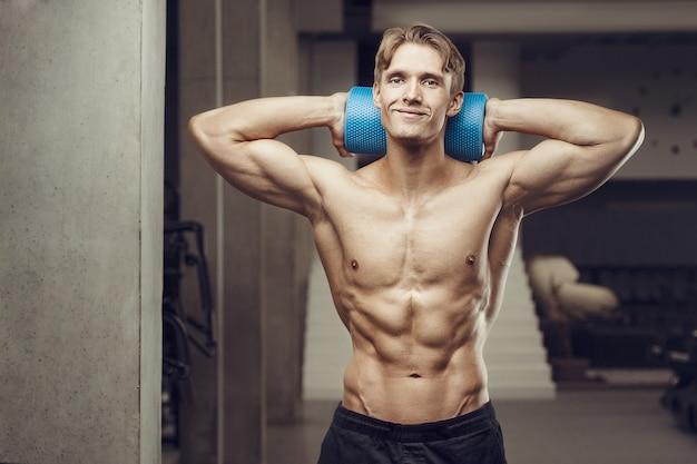 Uomo di forma fisica all'allenamento in palestra con rullo di massaggio che allunga i muscoli Foto Premium