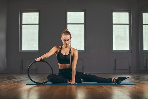 L'istruttore di fitness mostra gli esercizi con un espansore di gomma. la motivazione per un bel corpo. banner di fitness, copia spazio. Foto Premium