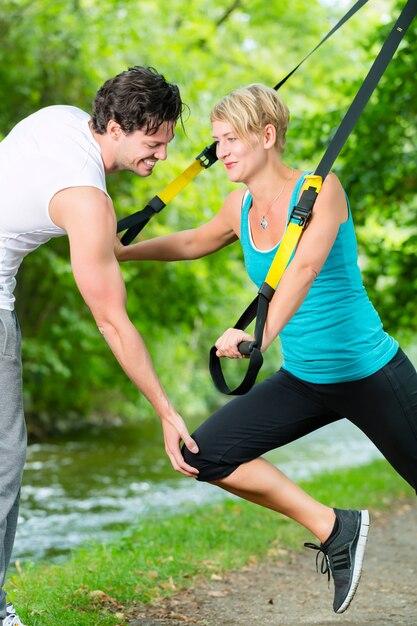Donna di forma fisica che si esercita con trainer di sospensione e personal trainer sportivo nel parco cittadino sotto gli alberi estivi Foto Premium