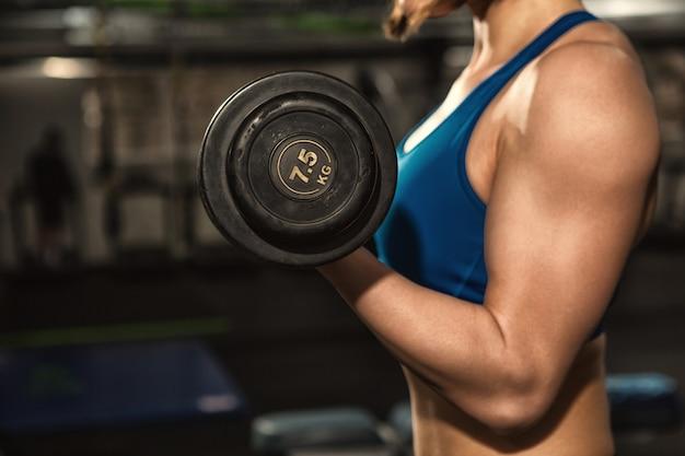 Fitness donna con corpo tonico in forma forte in abiti sportivi facendo riccioli bicipiti Foto Premium