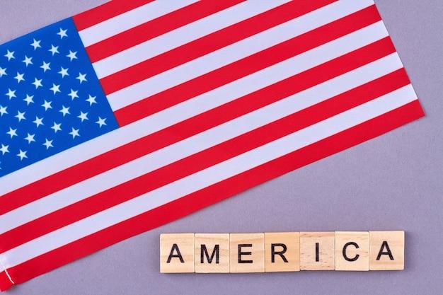 Bandiera degli stati uniti d'america. blocchetti di legno di alfabeto con lettere isolate su fondo viola. Foto Premium