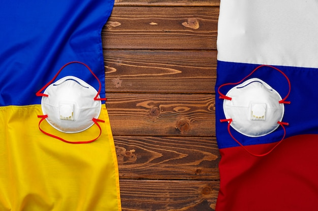 Bandiere di russia e ucraina su fondo in legno con maschere mediche Foto Premium