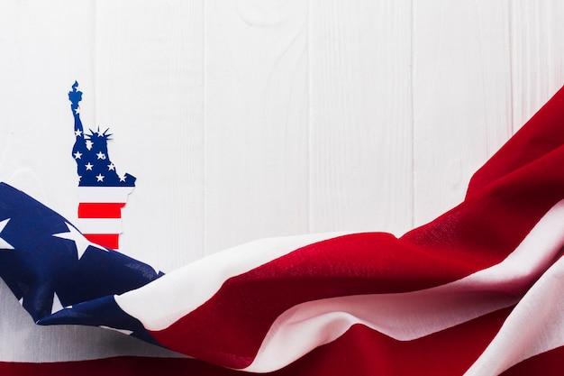 Disposizione piana della bandiera americana per la festa dell'indipendenza con la statua della libertà Foto Premium