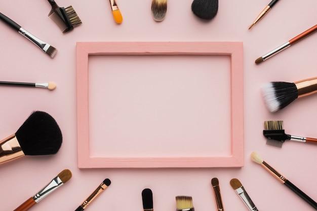 Disposizione piatta con pennello per il trucco e cornice rosa Foto Premium