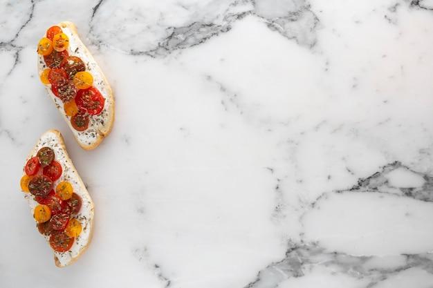 Focaccia con crema di formaggio e pomodorini su marmo con copia-spazio Foto Premium