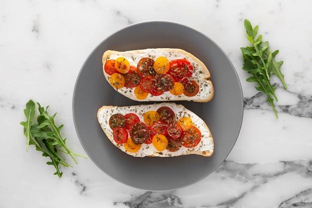 Pane piatto laici con crema di formaggio e pomodorini sul piatto Foto Premium
