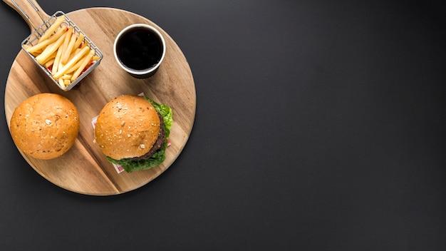 Lay piatto di hamburger e patatine fritte con spazio di copia Foto Premium