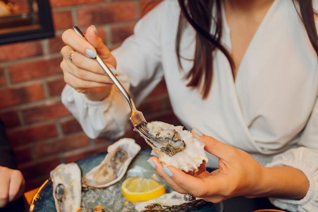 Lay piatto di mani caucasiche tenendo le ostriche con altri piatti di pesce su un tavolo scuro. Foto Premium