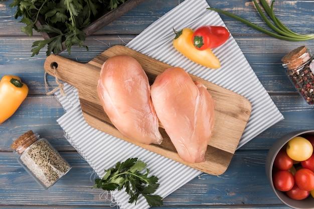 Petto di pollo piatto disteso su tavola di legno con ingredienti Foto Premium