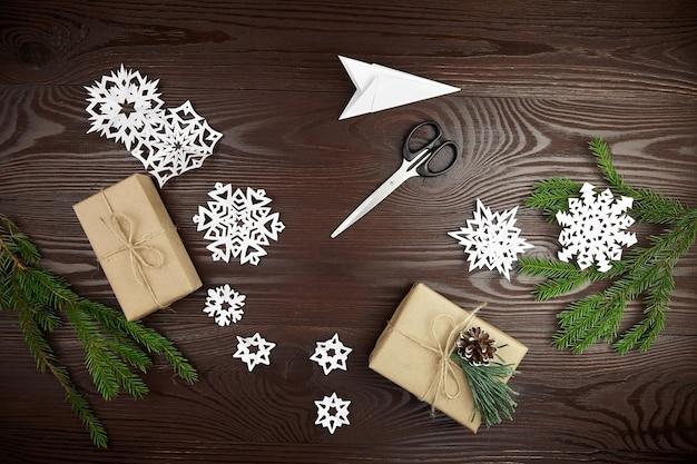 Composizione piatta per il taglio di fiocchi di neve di carta sul tavolo di legno Foto Premium