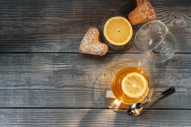 Composizione piatta laici con una tazza di tè, limone e muffin su un tavolo di legno Foto Premium