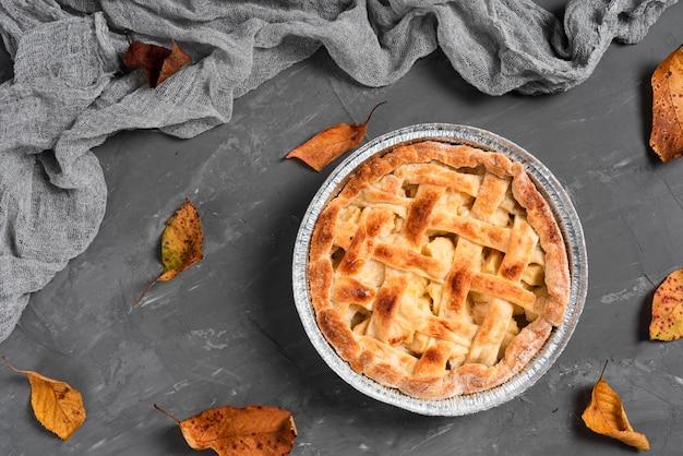 Piatto disteso di deliziosa torta circondata da foglie Foto Premium
