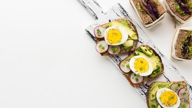 Lay piatto di panini con uova e avocado con spazio di copia Foto Premium
