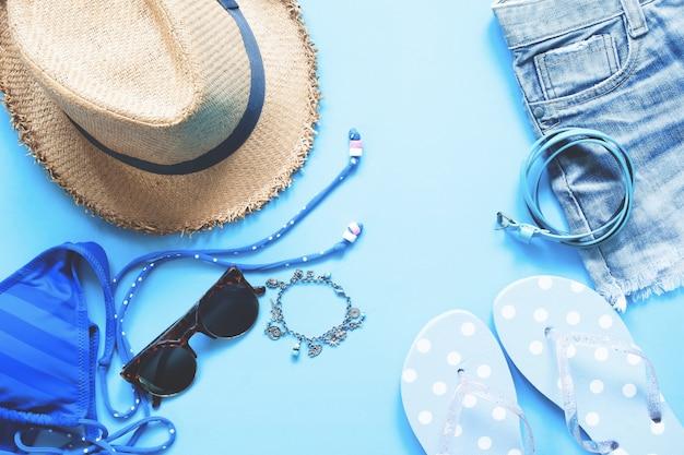 Piatto piano di accessori femminili su sfondo blu, concetto di moda primavera e estate Foto Premium