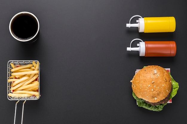 Piatto disteso di patatine fritte e hamburger con ketchup e senape Foto Premium