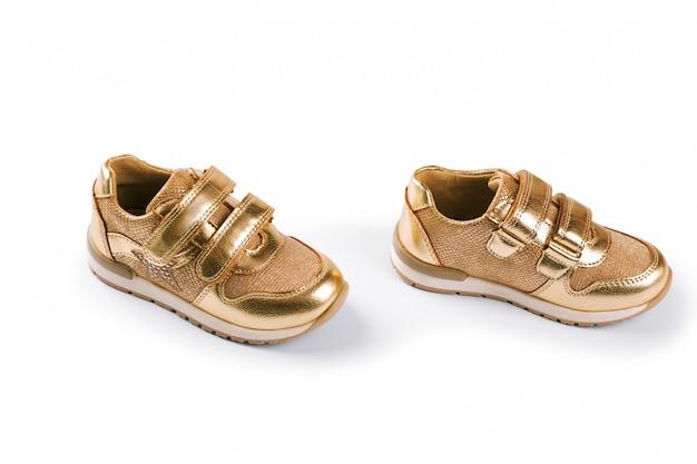 Distesi. le scarpe sportive per bambini d'oro isolate su bianco Foto Premium