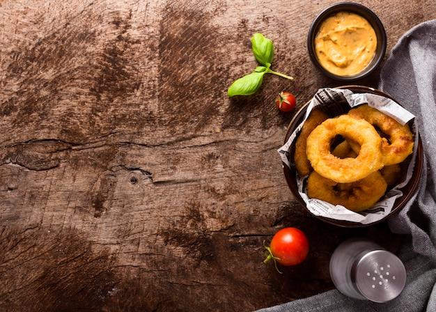 Piatto di laici ad anello patatine fritte nella ciotola con il pomodoro e lo spazio della copia Foto Premium