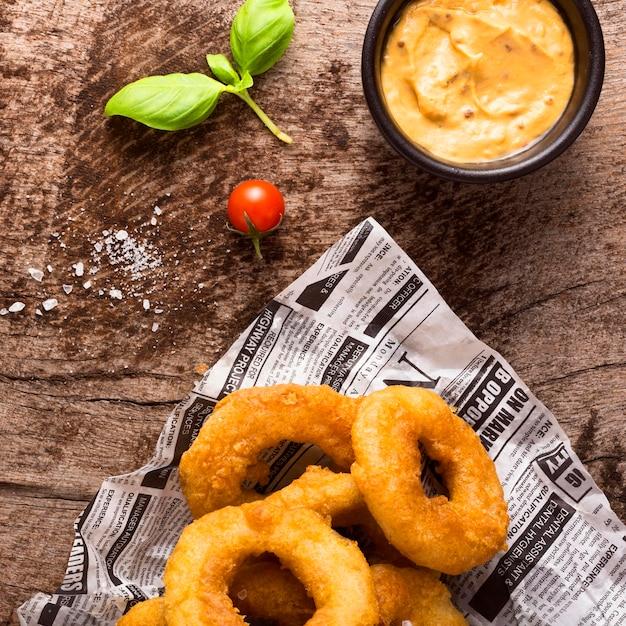 Lay piatto di patatine fritte ad anello sul giornale con senape Foto Premium