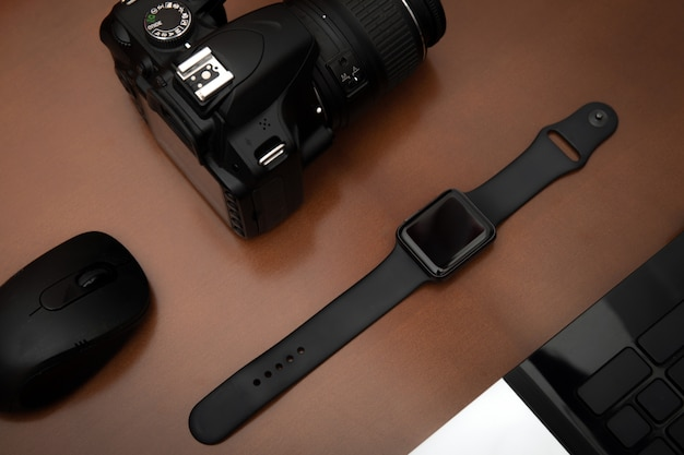 Disposizione piana degli oggetti techno per il lavoratore moderno con il telefono cellulare dello smartwatch e la macchina fotografica del dslr sulla tavola di legno. Foto Premium
