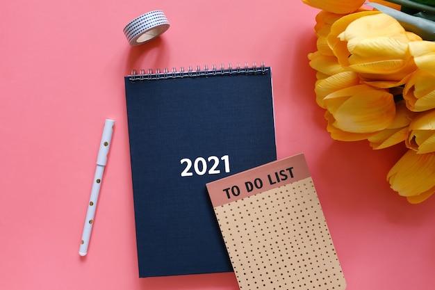Vista dall'alto piatto laico del diario o pianificatore nero 2021 con nota della lista delle cose da fare e cancelleria con fiore di tulipano giallo su sfondo rosso, concetto di risoluzioni del nuovo anno Foto Premium