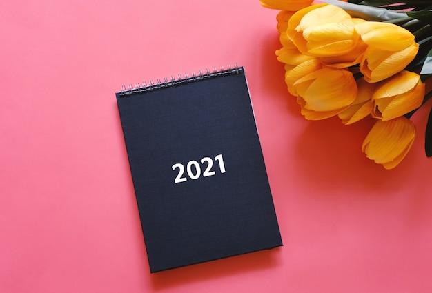 Vista dall'alto piatto laico del diario o pianificatore nero 2021 con fiore di tulipano giallo su sfondo rosso con spazio di copia, concetto di risoluzioni del nuovo anno Foto Premium