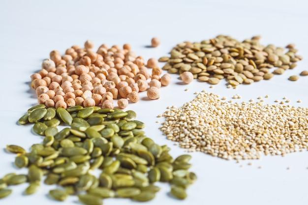 Lay piatto di varie proteine vegane. secco ceci crudi, lenticchie, quinoa e semi di zucca su uno sfondo bianco. Foto Premium