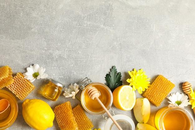 Piatto disteso con miele, fiori e frutti su grigio Foto Premium