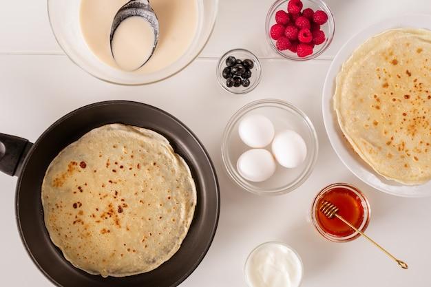 Layout piatto della padella con pancake, tre uova fresche nella ciotola, miele, panna acida, lamponi, more e pasta liquida sul tavolo Foto Premium