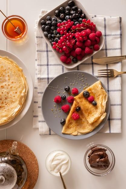 Layout piatto del tavolo della cucina servito per colazione con frutti di bosco freschi, frittelle appetitose, crema acida, miele e cioccolato da spalmare Foto Premium